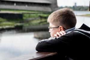 sad boy looking at the river